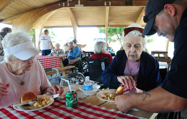 Salisbury: John Oliveira brings straws and napkins to Frances Trenholm, left, and Mary Cheney at Salisbury Beach State Reservation. The residents of Amesbury Village were taken to the beach for a cookout and fresh air along the Merrimack River. Bryan Eaton/Staff Photo