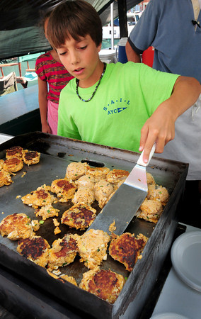 Newburyport: JD Pfingst, 12, of Salisbury flips lobster cakes in front of his father Steve, owner of David's and has a booth in the food court in Newburyort's Market Square. Bryan Eaton/Staff Photo