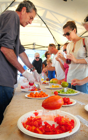 Newburyport: Newburyport Farmers' Market volunteer Don Jenner puts out samples of 20 varieties of tomato yesterday morning. Participating farms provided the tomatoes for the Tomato Festival which brought many people out to the event at the Tannery Marketplace. Bryan Eaton/Staff Photo