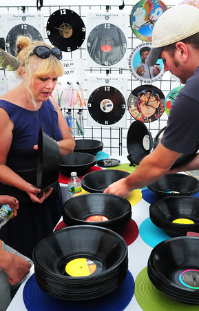 Newburyport: Sam Knight of Salisbury checks out vinyl records that have been pressed into bowls by Gary McAuslin of Blackberry Hill Designs at the Market Square Day Craft Show. They also make clocks from old records and several other handcrafted items. Bryan Eaton/Staff Photo