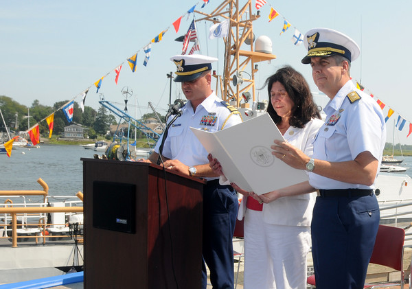 Newburyport Coast Guard Officer in Charge Jason Holm reads a proclimation declaring Newburyport a Coast Guard City as  Admiral Daniel Abel   and Mayor Donna Holaday read along at a ceremony on the Newburyports waterfront Saturday. Jim Vaiknoras/staff photo.
