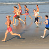 Salisbury: Runner cast long shadows as they hit the hard sand near the water at the annual Salisbury Life Guard 5 mile run on Salisbury Beach . Jim Vaiknoras/staff photo