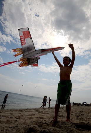 Salisbury: Andrew Gallagher, 7, of Andover , take advantage of the warm weather to fly an X-Wing fighter kite on Salisbury Beach Friday afternoon. Jim Vaiknoras/staff photo