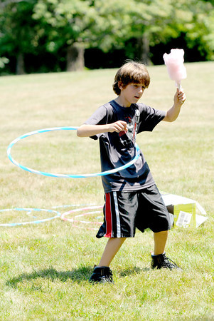 Ethan Cote, 9, of Boxford, enjoys some cotton candy as he Hula-hoops at Family Day in Maudslay Saturday. Jim Vaiknoras/staff photo