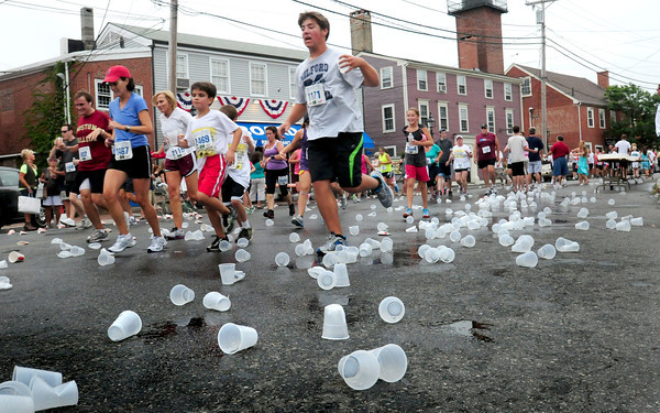 Newburyport: Runners in the Yankee Homecoming 5K Race head west on Water Street past discarded cups of water. Bryan Eaton/Staff Photo