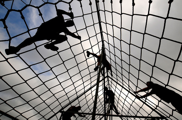 Amesbury: Runners in the Spartan Race at Amesbury Sports Park climb over a large net during the race Saturday. Jim Vaiknoras/staff photo