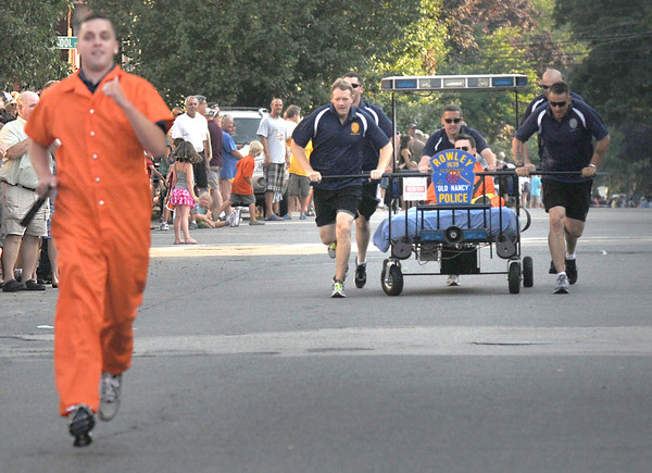 "Newburyport: The Rowley police chase their ""prisoner"" at the annual Yankee Homecoming Bed Race. Jim Vaiknoras/staff photo"