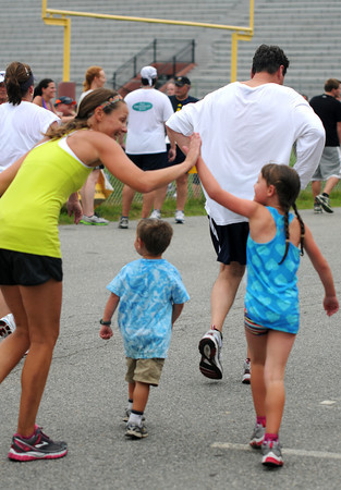 Newburyport: Patty Barera high fives her kids Olivia, 7, and Luke 4, after finishing the 5k Tuesday night at the annual Lions Club Race. Jim Vaiknoras/staff photo