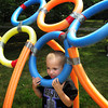Newburyport: Trevor Comora, 4, peeks through one of the rings of the Olympics symbol at Kids Day in the Park. Bryan Eaton/Staff Photo