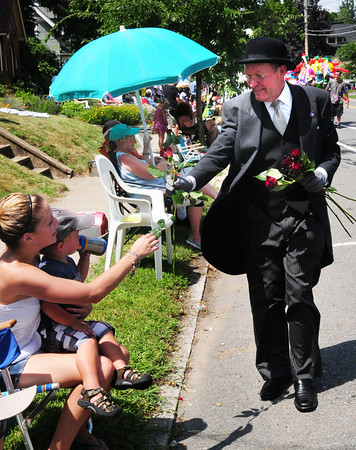 Newburyort: Local funeral director Paul Rogers rode in the Yankee Homecoming Parade in a vintage hearse, jumping out occasionally to give roses along the route. Bryan Eaton/Staff Photo