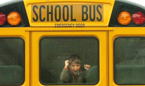 Amesbury: Hunter York, 7, spies some friends as his school bus pulls up to Amesbury Elementary School yesterday morning. Schools in Amesbury and the Triton Regional School District started classes for the year. Bryan Eaton/Staff Photo
