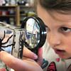Newburyport: Kendall Sanfacon, 6, uses a magnifying glass to study a funnel web spider in Melissa Duguie's class at the Brown School on Wednesday afternoon. The equipment was included in a discovery science cart loaded with hands on materials provided to the students by the Newburyport Education Fund. Bryan Eaton/Staff Photo <br /> , Newburyport: Kendall Sanfacon, 6, uses a magnifying glass to study a funnel web spider in Melissa Duguie's class at the Brown School on Wednesday afternoon. The equipment was included in a discovery science cart loaded with hands on materials provided to the students by the Newburyport Education Fund. Bryan Eaton/Staff Photo