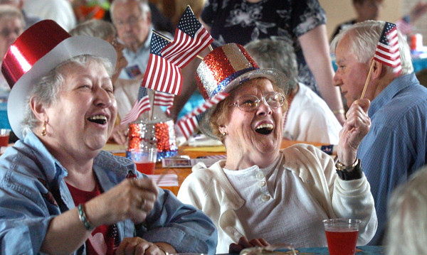 Amesbury: Dorothy Caberly, left, and Laurie Vigneault, both of Amesbury wave American Flags yesterday afternoon. They were at the Patriotic-themed Amesbury Days Senior Citizen's Cookout. Bryan Eaton/Staff Photo