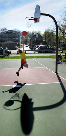 Newburyport: Griffin Dupuis, 6, of Rowley goes for a layup at Cashman Park in Newburyport on Tuesday afternoon. His mother, Jeanine, was giving him some pointers at the school vacation-packed playground. Bryan Eaton/Staff Photo