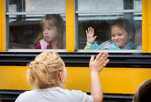 Amesbury: <br /> Isabella Fusco, 6, waves to her mother, Shelley, as she and her friend, Ally Wilson, 7, pull up to Amesbury Elementary School. Her mom met her at the school to take pictures of her getting off the bus.<br /> Photo by Bryan Eaton/Newburyport Daily News. Tuesday, August 29, 2006