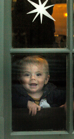 Newburyport: Gregory Giuntini, 7 months, of Newburyport has a big smile for passersby as he peers out the window of Starbucks in Newburyport's Market Square. He was there with his mother, Elizabeth, and grandmother Nancyk Giuntini who was up visiting from Pennsylvania for Christmas. Bryan Eaton/Staff Photo