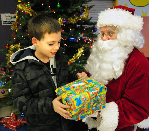 Salisbury: Sam Bagley, 7, receives a gift from Santa Claus who made a stop at the Boys and Girls Club in Salisbury as he and others also had some pizza. The Pentucket Middle School Community Program donated the presents. Bryan Eaton/Staff Photo