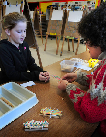 Newburyport: Sydney Turner, 8, hands the pieces of her sled made from popsicle sticks to Bresnahan School principal Kristina Davis who was helping out in art class. The children decorated the top of the sled and handed them to be put together with a glue gun, the sleds to be taken home for ornaments. Bryan Eaton/Staff Photo