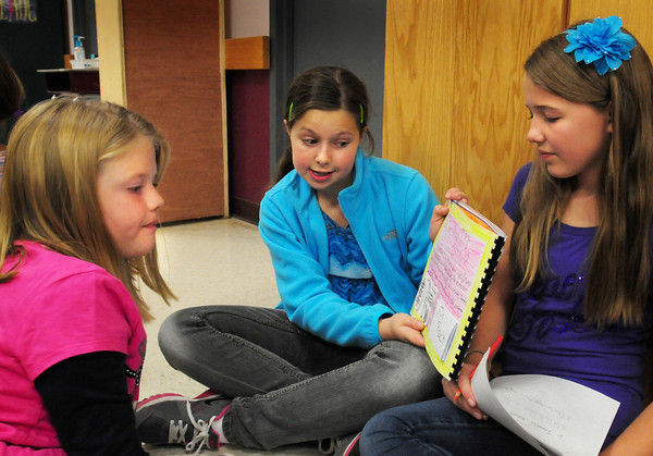 """Amesbury: Amesbury Middle Schooler Hanna Scotch, 11, center, reads her book """"Why Was the Discovery of King Tut's Tomb Important"""" with classmate Ashley York, 12, to Peyton Searles, 8, at the Cashman School in Amesbury. The sixth-graders have been learning about ancient Egypt in their language arts and social studies classes and traveled to the Cashman School to read thier informational books to them. Bryan Eaton/Staff Photo"""