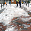 Newburyport: Johnny Corcoran, right, and Nick Goodwin of the Newburyport Department of Public Services clean off the slushy mess in Market Square yesterday morning. Only rain is expected today to melt what snow and ice remains with clearing expected tomorrow. Bryan Eaton/Staff Photo