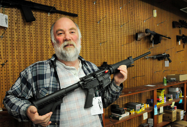 "Salisbury: Bob Bernstein owner of the The Original Bob's Tactical Gun Shop on Route One in Salisbury shows off one of the few ""assault type"" rifles left. The display board behind him was full until recently as there has been a run on the weapon. Bryan Eaton/Staff Photo"