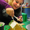 Newburyport: Kaylee Hawkes, 13, adds more frosting to the roof of her gingerbread house in which to attach more M&M's to. She was in the Newburyport Library afterschool program for teens and tweens. Bryan Eaton/Staff Photo