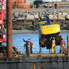 Hampton: A  John Deere excavator is lifted onto a barge yesterday morning that had been submerged in the Hampton River next to the Hampton Bridge. The piece of equipment was being used in the dredging of Seabrook Harbor fell off a barge last week that was taking on water and listing. Bryan Eaton/Staff Photo