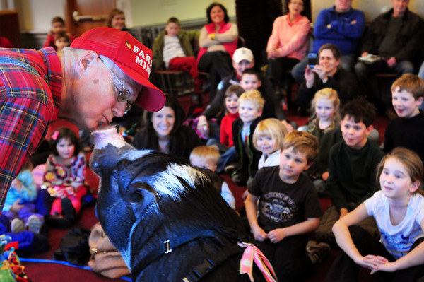 "Newburyport: Farmer Miner of Bristol, Conn. kisses his pig, Daisy II at the Newburyport Public Library on Thursday afternoon. He was presenting the program ""Pig Out on Reading"" where he told stories, read a book about pigs and introduced Daisy II to encourage the youngsters in attendance that reading is fun and informative. Bryan Eaton/Staff Photo"