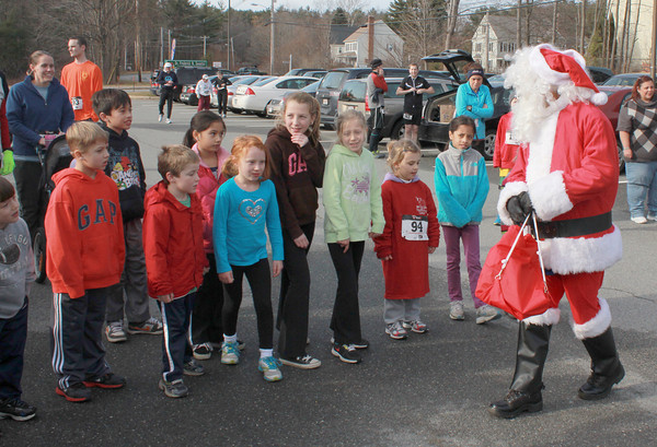 Merrimac: Santa gives race instructionto runners in teh Elf Run abefore the start of the 18th annual Winner's Circle Running Club Santa's Toy Trot at the Sweetsir Shool in Merrimac Sunday. Jim Vaikoras/staff photo