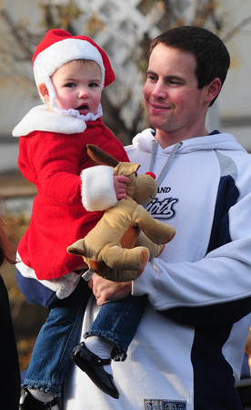 Merrimac: Bill Thompson hold his daughter Keira as they watch the annual Merrimac Santa Parade Sunday. JIm Vaiknoras/staff photo