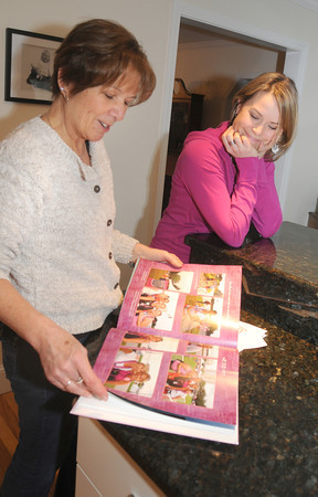 Amesbury: Mother and daughter Helen and Lisa Nadeau, of Amesbury, look through a book of photographs about their history with the Susan G. Komen 3-day walk to support breast cancer research. Jim Vaiknoras/staff photo