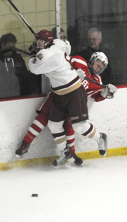 Newburyport: Newburyport's Connor Wile checks Saugus's Anthony Cieri during their game at the Graf Rink in Newburyport. Jim Vaiknoras/staff photo