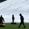 Amesbury: Tubers on school vacation walk along the green artificial turf at the Amesbury Sports Park are silhouetted by the only snow in the area, other then the Ski Bradford in Haverhill. Bryan Eaton/Staff Photo