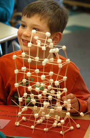 "Newbury: Second-grader Lukas Carmana, 7, shows off his ""fire temple"" he built with classmate Louis Bohlen, 7, on Tuesday. Students in Mary Ann Fraser's class at Newbury Elementary School made scuptures using 100 marshmallows for the 100th day of school which was Monday. Bryan Eaton/Staff Photo"
