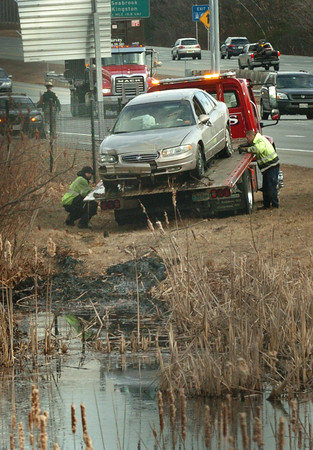 Salisbury: One person was injured in this car that ended up in a pond on the southbound lane of Interstate 95 in Salisbury at the Maria Miles Rest Area yesterday morning. Bryan Eaton/Staff Photo