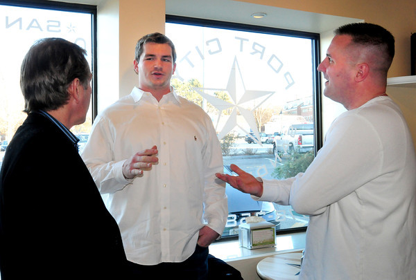 Newburyport: New England Patriot Rich Ohrnberger, center, talks with Tyke Karopoulos at the opening of his new shop Port City Sandwich Co., right and property owner David Murphy. Bryan Eaton/Staff Photo