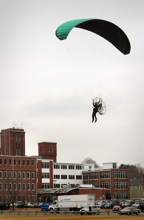 Newburyport: Patrick Tarmey brings in powered parachute to a landing at Cashman Park in Newburyport near the Towle Building after a couple loops over the Merrimack River. Bryan Eaton/Staff Photo
