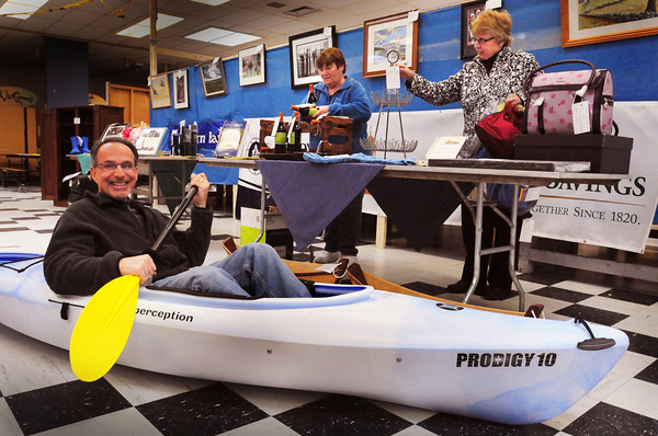 Newburyport: Mike Zerigian shows off a kayak as other volunteers, Kathy Eaton, left, and Mary Zerigian put items for Opportunity Works Lend-a-Hand Auction. The auction, at the Nock Middle School is tomorrow, but a showing off of items was held last night. Bryan Eaton/Staff Photo