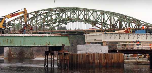 Amesbury: Contruction crews work on the center span, right, of the Hines Bridge in the shadow of the Whittier Bridge. An old section of the bridge remains to the left for now. Bryan Eaton/Staff Photo