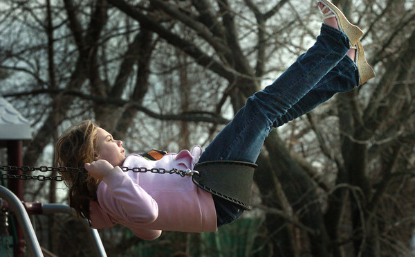 Salisbury: Olivia Dalton, 11, shoots for the sky on the swingset at the Memorial School yesterday as many children at the Boys and Girls Club went outside during the nice weather. Bryan Eaton/Staff Photo
