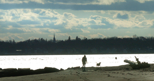 Salisbury: A human and canine walk along the Merrimack River at Salisbury Beach State Reservation during the warm, though blustery weather Thursday afternoon. After the rain that came overnight, the weather cools for Saturday with more wind. Bryan Eaton/Staff Photo