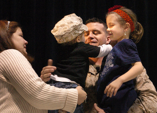 Rowley: Julie McCann hands her husband, Steve, their son, Cole, while holding their daughter Isabelle who's a kindergartner at the Pine Grove School in Rowley yesterday afternoon. The soldier who just returned from Afghanistan surprised Isabelle in a small assembly of her classmates. Bryan Eaton/Staff Photo