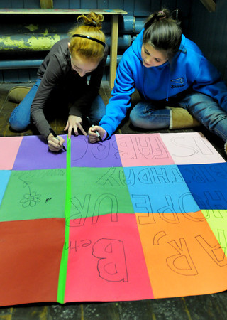 Newburyport: Liane Wilson, left, and Olivia Giunta, both 12, hide in a side room at the Kelley School Youth Center while making a giant birthday card. The card was for Beth Manning, youth coordinator at the youth center who's celebrating tomorrow, though they were going to present the card last night. Bryan Eaton/Staff Photo
