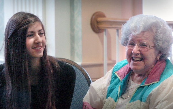 Newburyport: Claudia Runk, 13, and Louise Carty laugh over the spelling of a word at Atria Merrimack Place on Wednesday afternoon. Students of the Kelley School Teen Center visited the residents there and joined them in a spelling bee. Bryan Eaton/Staff Photo