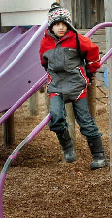 Amesbury: Ryan Ghezzi, 8, slides down some playground equipment at the Amesbury Elementary School late yesterday afternoon. He was in the Amesbury Recreation Department's afterschool program where they spent some time outside in the milder than normal temperatures. Bryan Eaton/Staff Photo