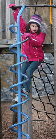 Amesbury: Sarah Chase, 7, works her way down some playground equipment outside Amesbury Elementary School on Monday afternoon after snack time. She was in the Amesbury Recreational Department's afterschool program with friends before going inside for other activities. Bryan Eaton/Staff Photo
