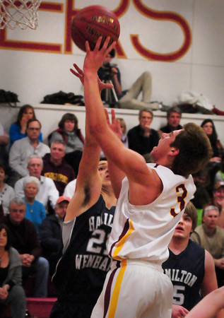 Newburyport: Newburyport's Colton Fontaine flies for two points past a Hamilton-Wenham defender. Bryan Eaton/Staff Photo
