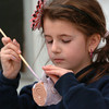 """Salisbury: Emily Johnson, 9, applies glaze to a cup she made of pottery she made at the Salisbury Elementary Afterschool Program """"Explorations"""" on Monday. The six-week course was given by Lauren Griffin, a former student there, who studied pottery in college. Bryan Eaton/Staff Photo"""