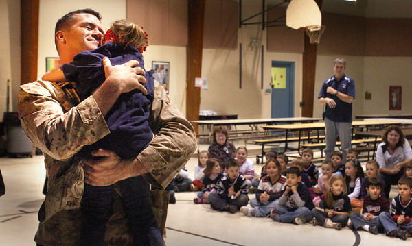 Rowley: Steve McCann hugs his daughter Isabelle in front of her fellow kindergartners at the Pine Grove School in Rowley yesterday afternoon. The soldier returned early yesterday morning from a tour in Afghanistan and wanted to surprise Isabelle who thought he wasn't coming home until May. Bryan Eaton/Staff Photo