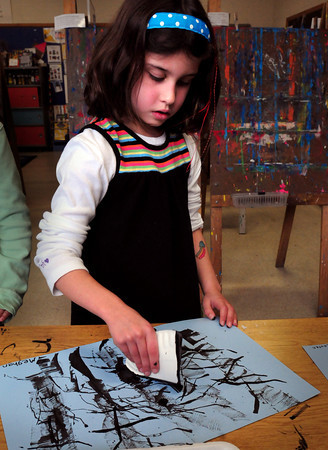 """Newburyport: Meghan Murray, 7, uses a quarter piece of a paper plate to create a wintry tree scene with ink in art class at the Bresnahan School in Newburyport on Thursday morning. The children were read the book """"Strangers in the Woods"""" about different animals who spend the winter there. Bryan Eaton/Staff Photo"""